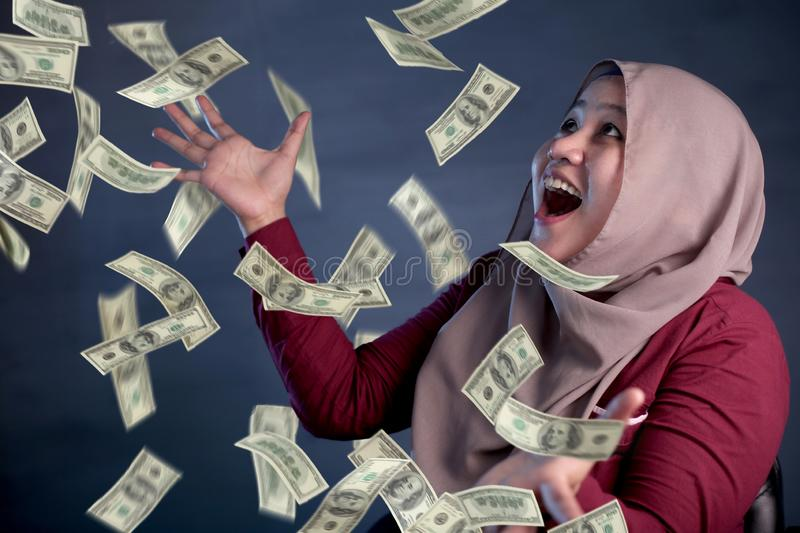 Young Woman Under Rain of Money. Portrait of happy successful young Asian billionaire muslim woman smiling happily under rain of money. Wealth investment royalty free stock photos