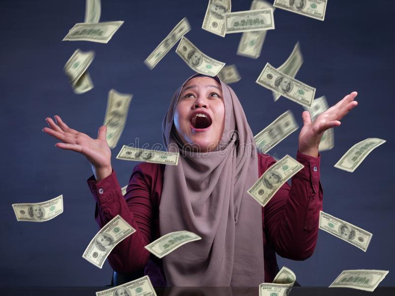 Young Woman Under Rain of Money. Portrait of happy successful young Asian billionaire muslim woman smiling happily under rain of money. Wealth investment royalty free stock photo
