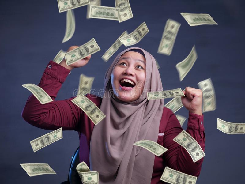 Young Woman Under Rain of Money. Portrait of happy successful young Asian billionaire muslim woman smiling happily under rain of money. Wealth investment stock images