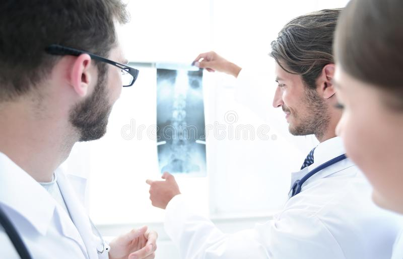 Portrait of happy surgeons holding x-ray report. Back view of a doctor and a patient examining an x-ray together stock photo