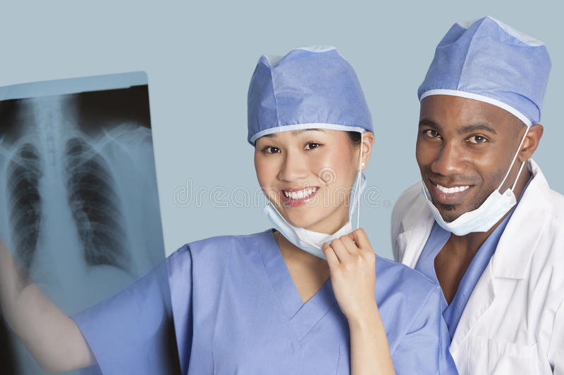 Portrait of happy surgeons holding x-ray report over light blue background royalty free stock photography