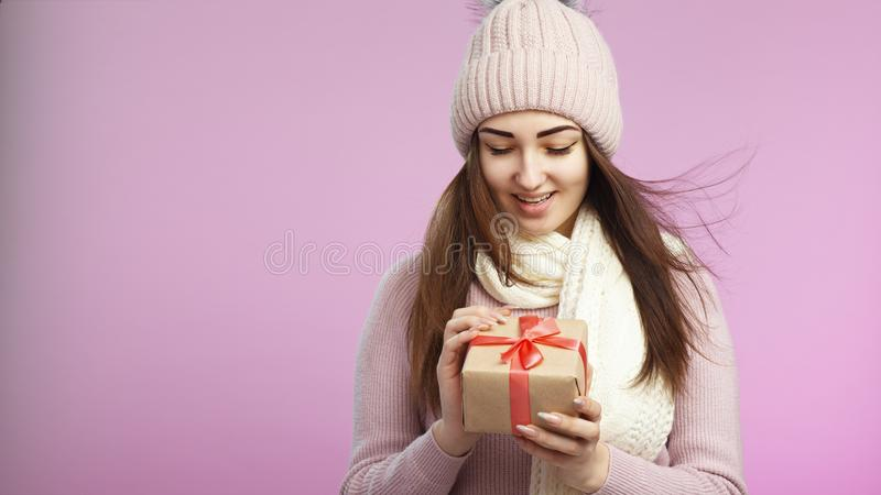 Portrait of happy surprised girl opening gift box in decorative craft paper, young woman in knitted hat and scarf on a pink stock photos