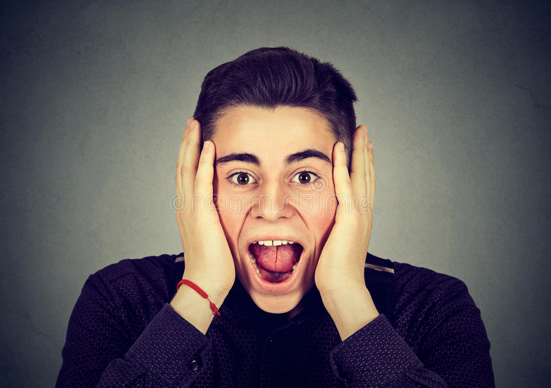 Portrait of a happy surprised man screaming. Surprised young funny looking man screaming royalty free stock images