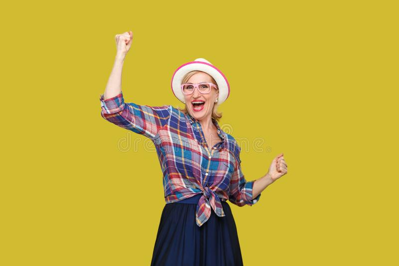 Portrait of happy surprised modern stylish mature woman in casual style with hat and eyeglasses standing and celebrating her. Victory and looking at camera stock image