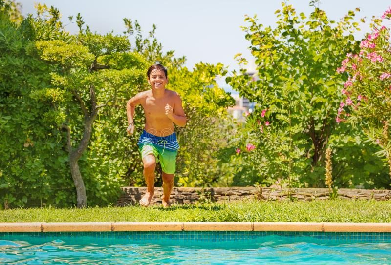 Happy teenage boy running to the swimming pool stock images