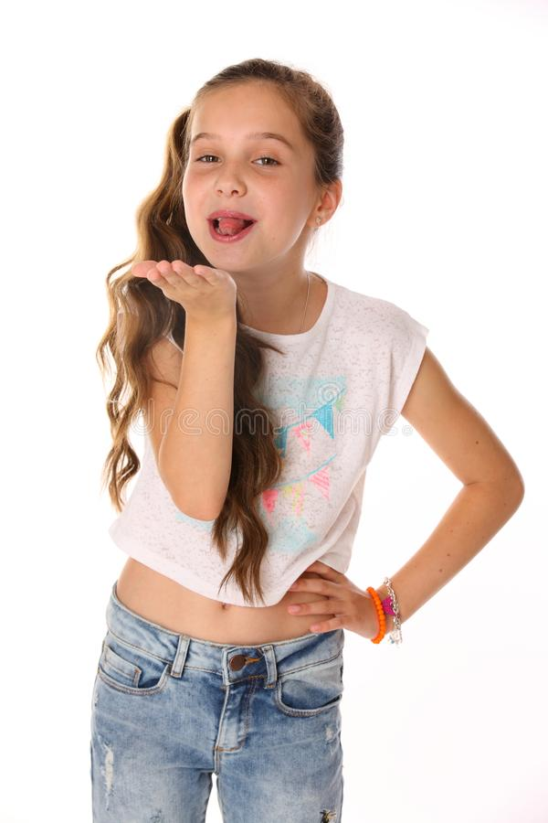 Portrait of happy teenage girl in blue jeans with a bare belly. Portrait of happy slender cheerful teenage girl. The child elegantly poses makes funny faces and stock photography