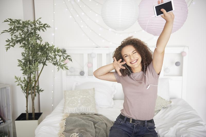 Portrait of happy teenage girl listening to music and dancing stock photography