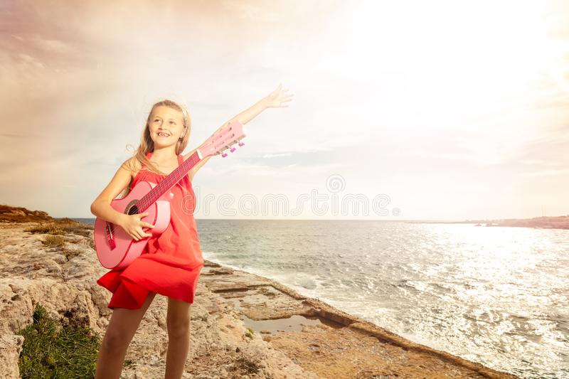 Happy teenage girl playing guitar at the seaside stock photography