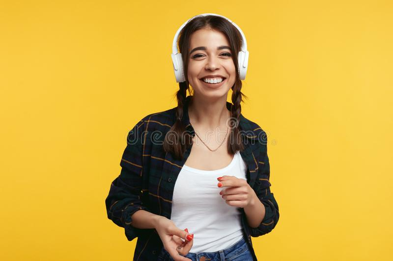 Happy teenager with white headphones, listens music and feels glad, smiling with broad smile showing her perfect teeth stock photo