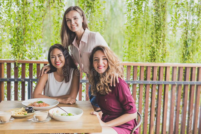 Happy three best friend having their lunch together at a cafe royalty free stock photo