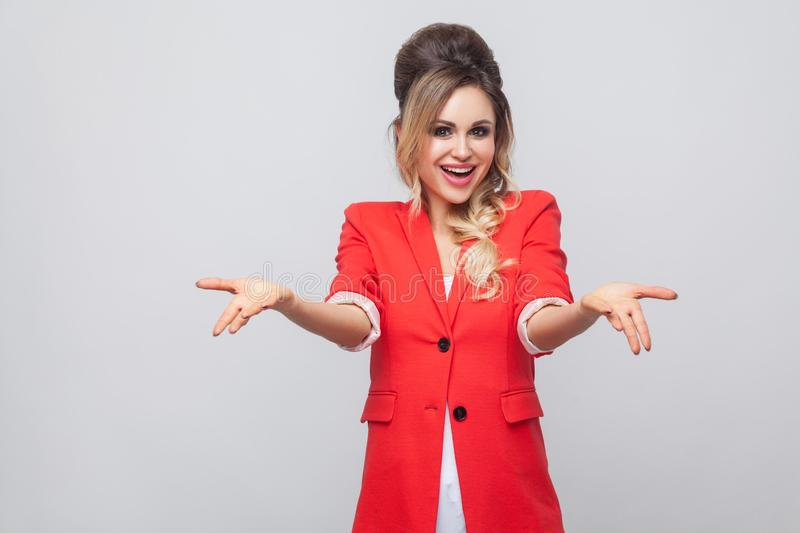 Portrait of happy toothy smiley beautiful business lady with hairstyle and makeup in red fancy blazer, standing and looking at. Camera with raised arms. indoor royalty free stock photos