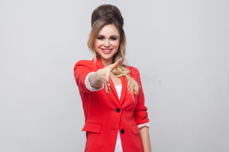 Portrait of happy toothy smiley beautiful business lady with hairstyle and makeup in red fancy blazer, standing, looking at camea. And giving hand to greeting royalty free stock photography