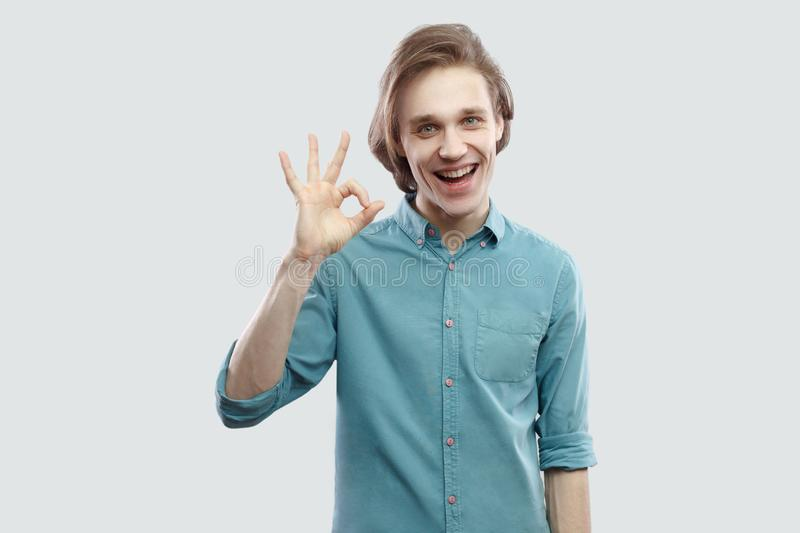 Portrait of happy toothy smiley handsome long haired blonde young man in blue casual shirt standing and looking at camera with ok stock image