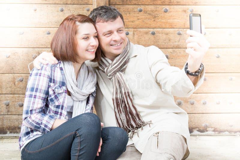 Portrait of happy tourist couple taking a selfie royalty free stock photos