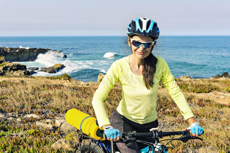 Portrait of a happy tourist cyclist on the background of ocean, stock photography