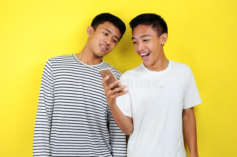 Portrait of happy two casual men smiling look at smartphone. Portrait of handsome two young men looking at their phone and smiling royalty free stock image