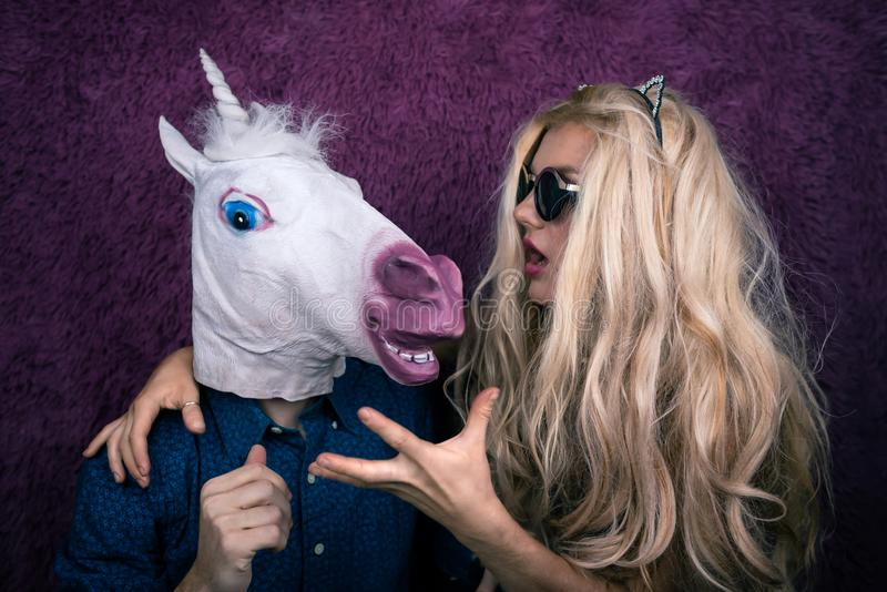 Portrait of happy unicorn in the arms of freaky young woman stock image