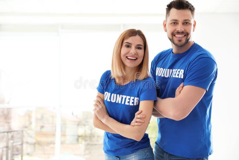 Portrait of happy volunteers in uniform indoors stock photography