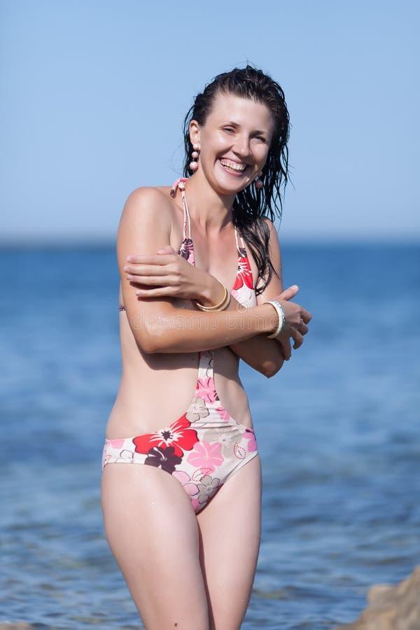 Portrait of happy wet girl in one-piece swimwear against sea stock photo
