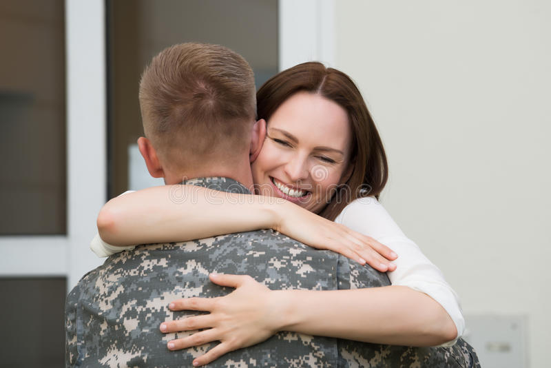 Happy Wife Hugging Her Husband. Portrait Of Happy Wife Hugging Her Husband In Army Uniform royalty free stock photography