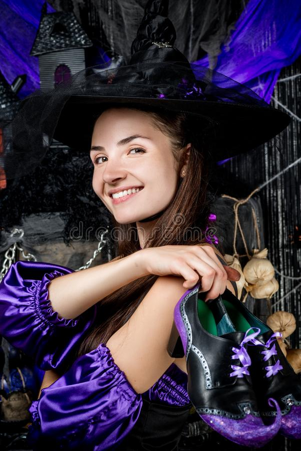 Portrait of a happy witch in a suit with shoes on a black stock images