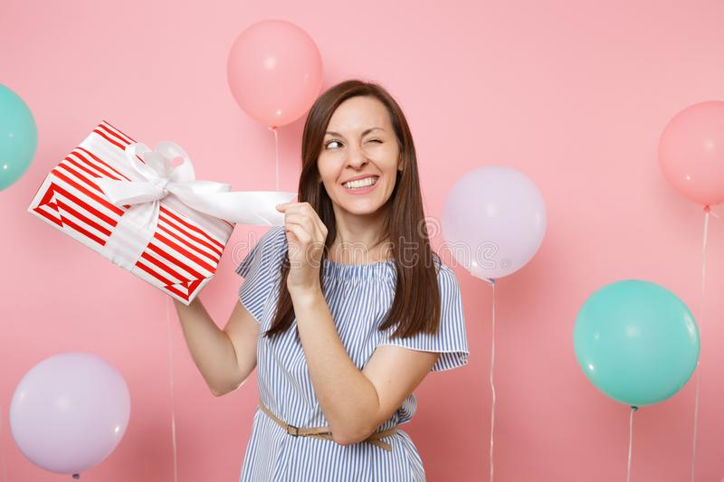 Portrait of happy woman in blue dress blinking untying bow on red box with gift present on pastel pink background with royalty free stock photo
