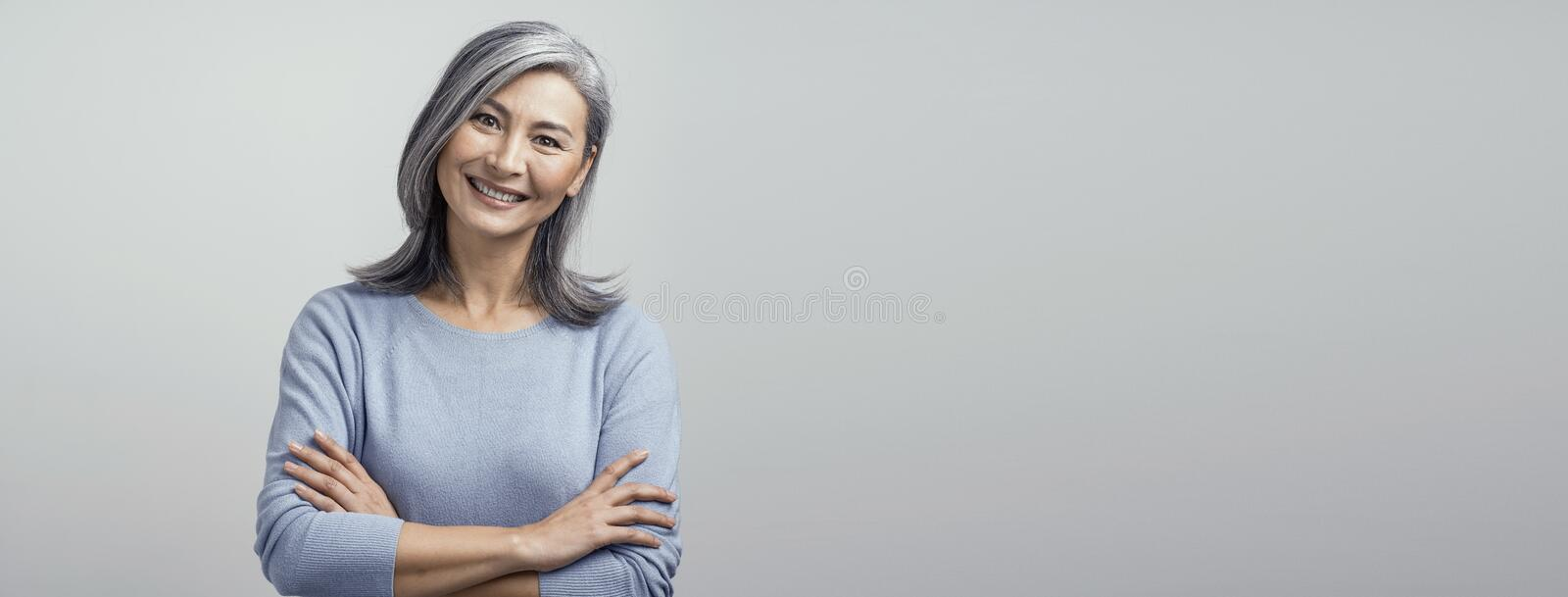 Smiling Asian senior woman with crossed arms royalty free stock images