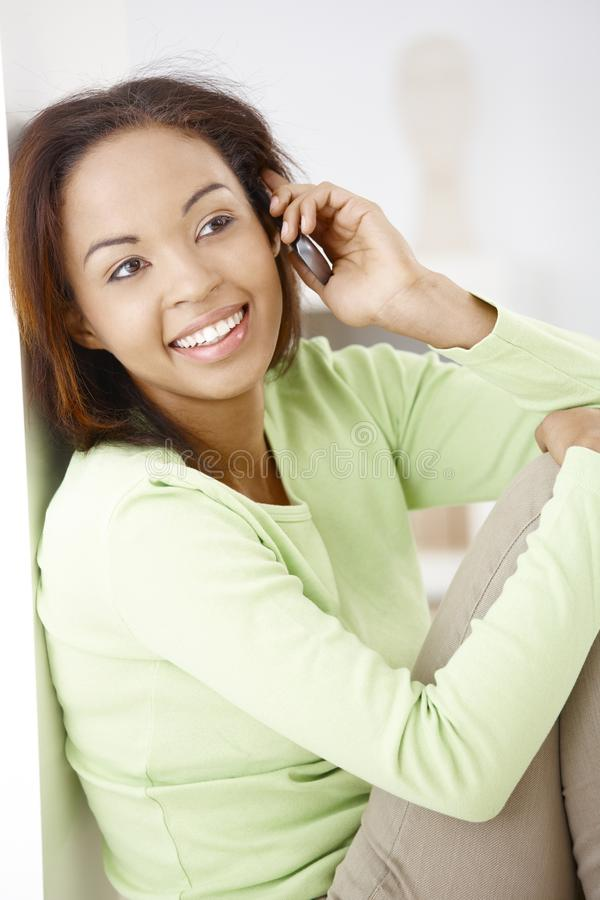 Portrait of happy woman on call. Portrait of happy attractive afro woman on mobile phone call, smiling royalty free stock photography