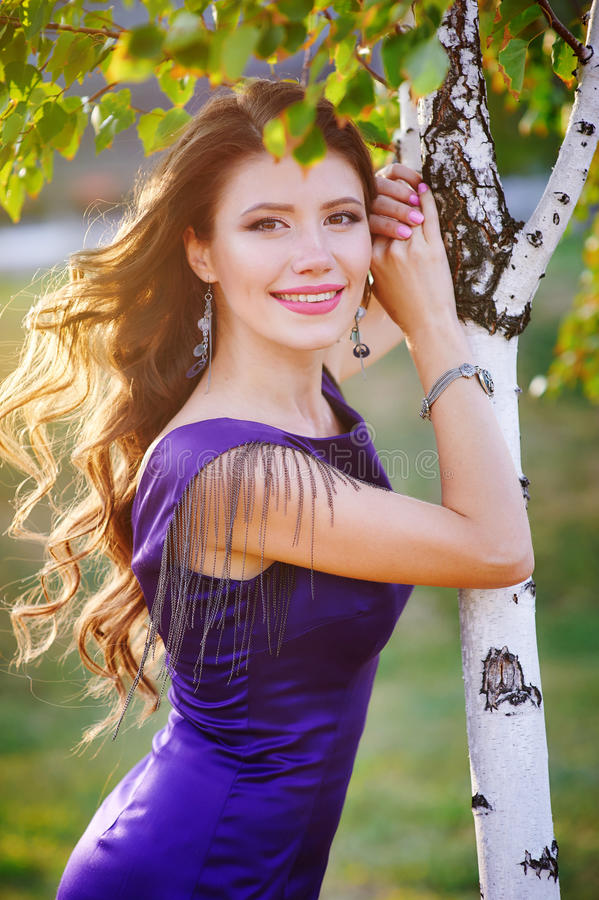Portrait of happy woman with curled hair outdoors near birch in sunset sun.  stock images