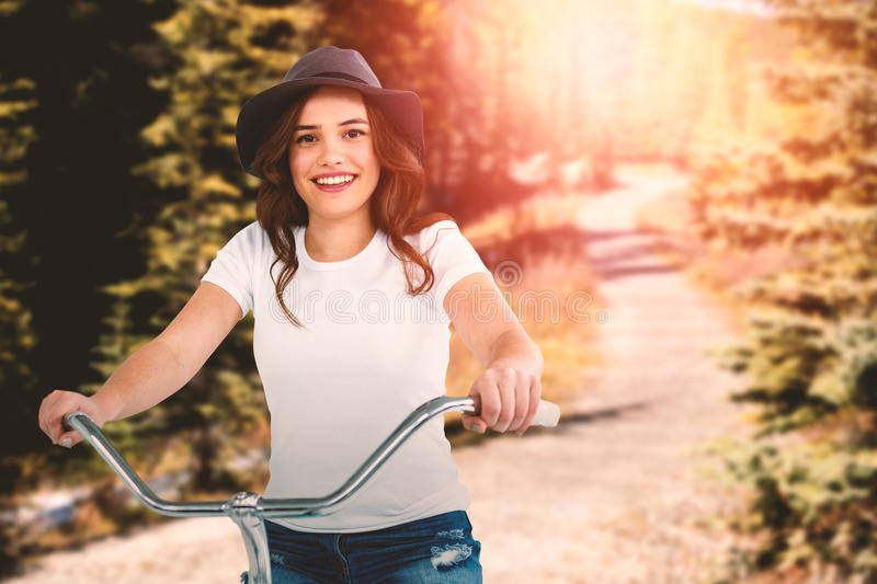 Composite image of portrait of happy woman cycling on bicycle stock images