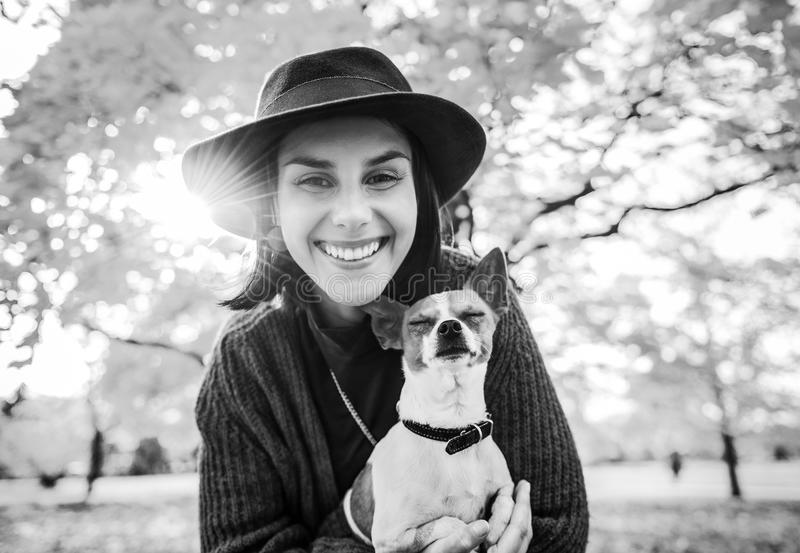 Portrait of happy woman with dog outdoors in autumn royalty free stock images