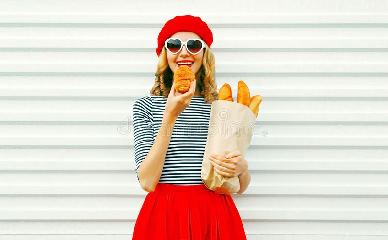 Portrait happy woman eating croissant holding paper bag with lon royalty free stock image