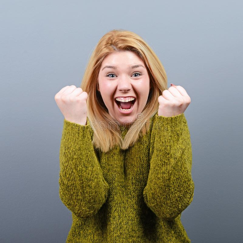 Portrait of happy woman exults pumping fists ecstatic celebrates success against gray background royalty free stock images