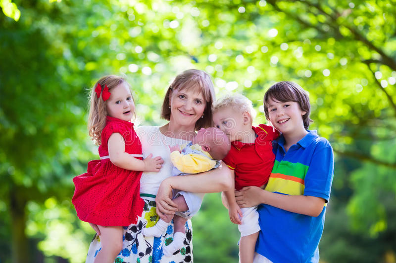 Portrait of happy woman with four kids. Mother and children play in a park. Woman with newborn baby, little girl, toddler and teenager boy. Siblings with big age royalty free stock image