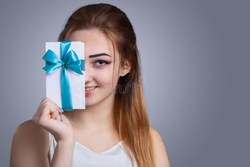 Portrait of a happy woman with a gift box in her hands on a studio background, the girl covers half of her face with present with royalty free stock image