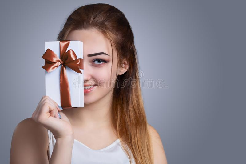 Portrait of a happy woman with a gift box in her hands on a studio background, the girl hide half of her face with present and royalty free stock photo