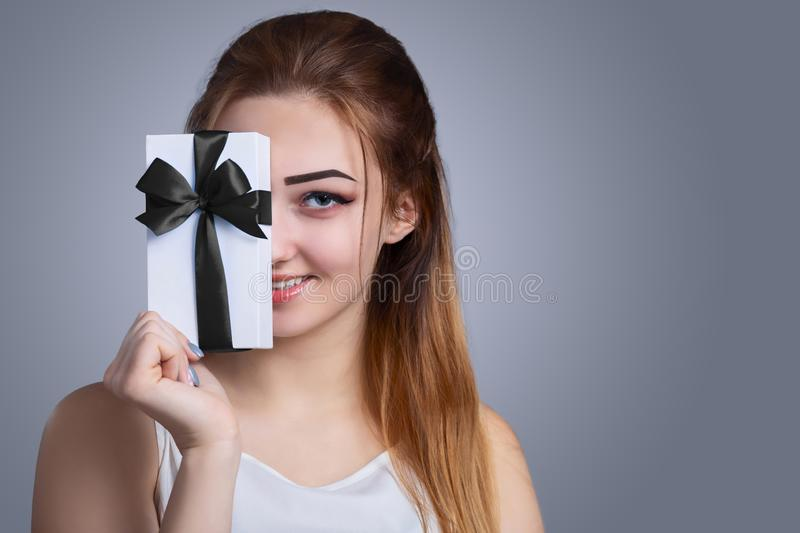 Portrait of a happy woman with a gift box in her hands on a studio background, the girl hide half of her face with present with a royalty free stock photos