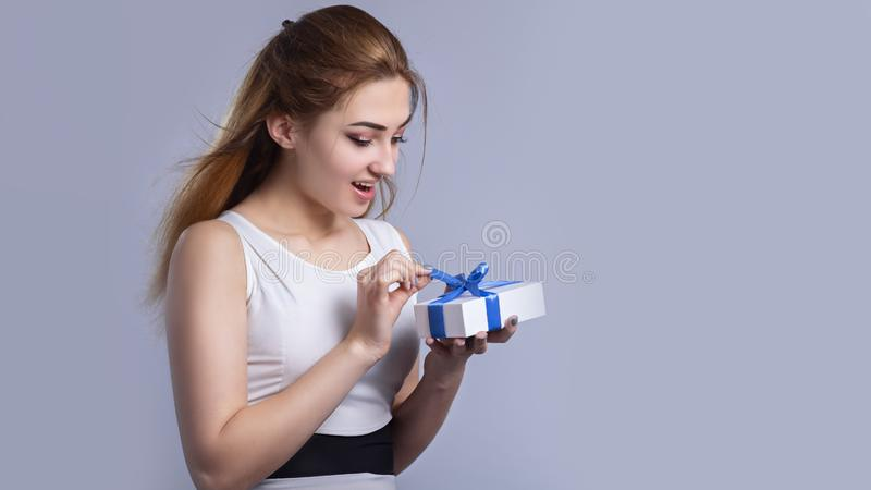 Portrait of a happy woman with a gift box in her hands on a studio background, the girl hide half of her face with present and royalty free stock photos