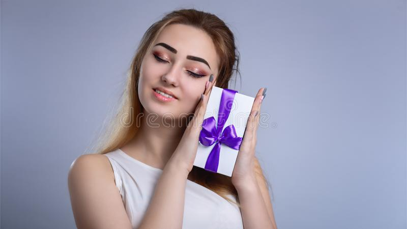 Portrait of a happy woman with a gift box in her hands on a studio background, the girl hide half of her face with present and stock photography