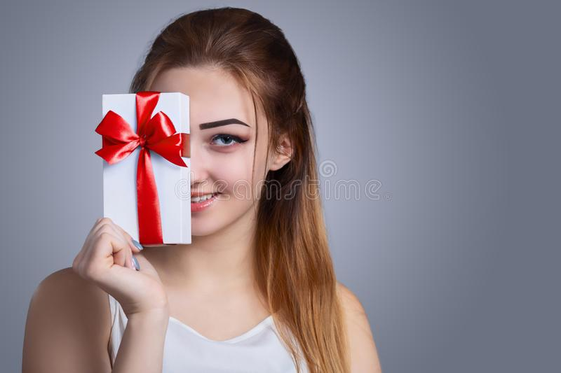 Portrait of a happy woman with a gift box in her hands on a studio background, the girl hide half of her face with present and stock photo