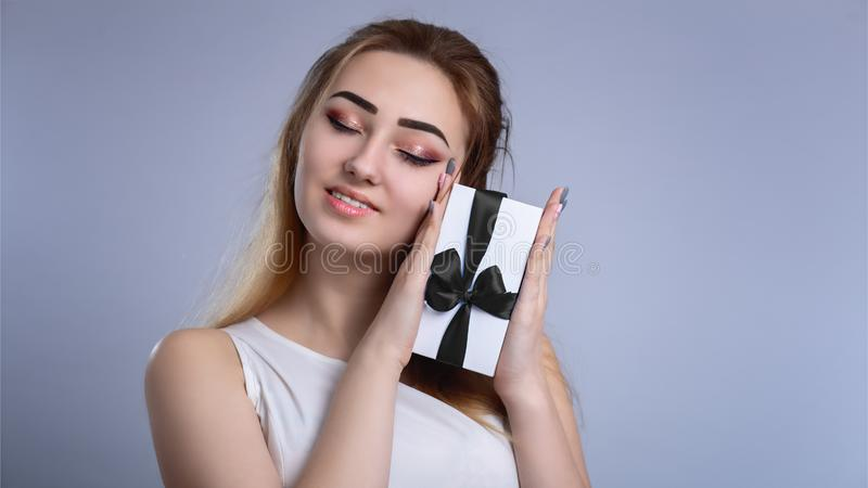 Portrait of a happy woman with a gift box near the face on a studio background, the girl closed her eyes from pleasure and pressed stock image