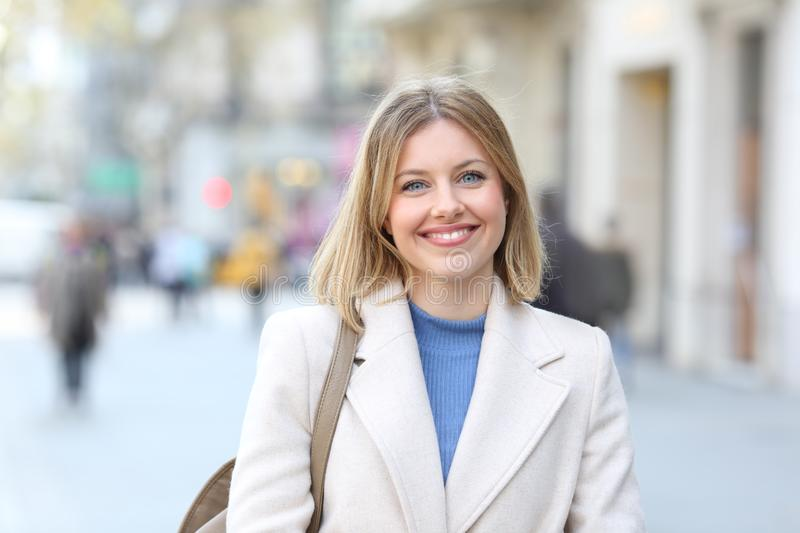 Portrait of a happy woman looking at camera in the street. Front view portrait of a happy woman looking at camera standing in the street royalty free stock images