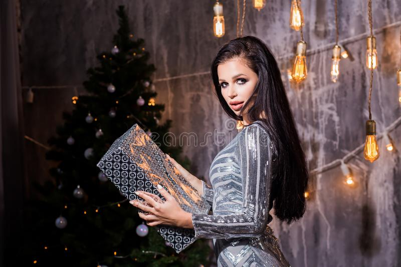 Portrait of a happy woman opening gift box and looking at camera over gray background. Holidays, New Year, celebration and people concept royalty free stock images