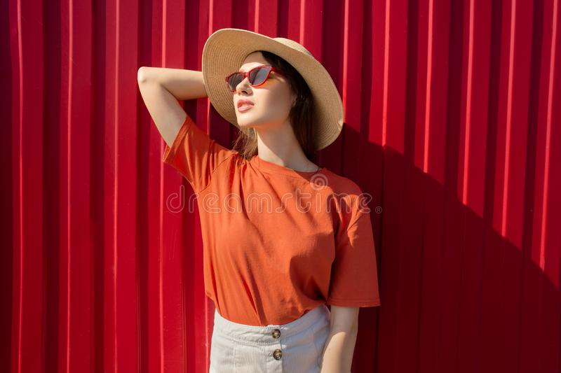 Portrait of a happy woman opposite her red wall. Natural smile. Sunny day. Bright stylish photo stock photo