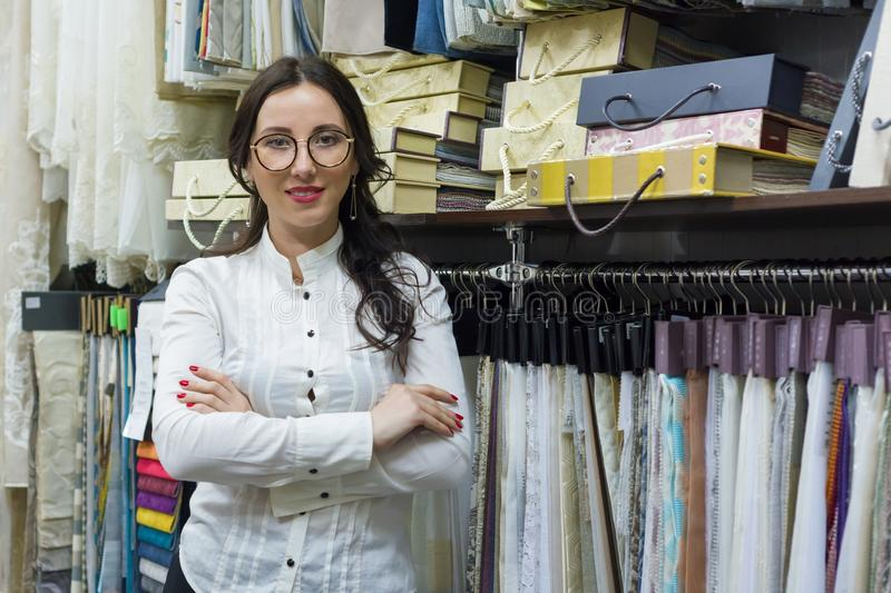 Portrait of happy woman owner with crossed arms in interior fabrics store, background fabric samples. Small business home textile royalty free stock images