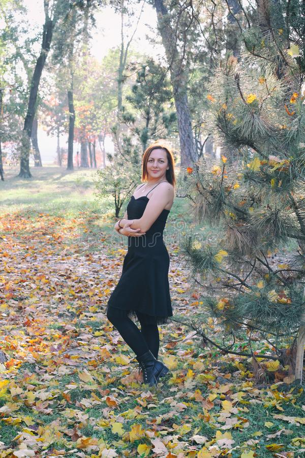 Portrait of a happy woman playing with autumn leaves in forest royalty free stock image