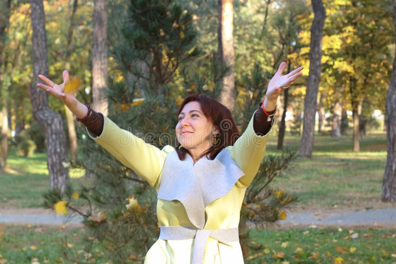 Portrait of a happy woman playing with autumn leaves in forest royalty free stock photography