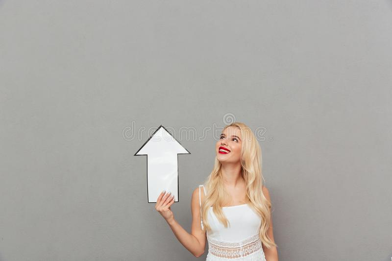 Portrait of a happy woman pointing away with an arrow and looking at camera over gray background. Portrait of a happy woman pointing up with an arrow over gray royalty free stock images
