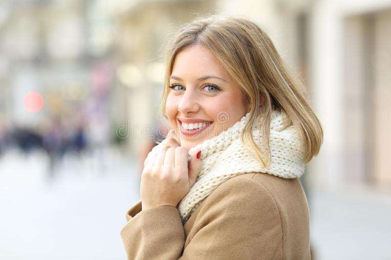 Happy woman posing looking at camera in winter in the street. Portrait of a happy woman posing looking at camera in winter in the street stock images