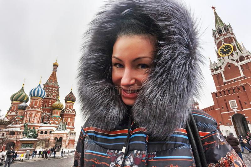 Portrait of a happy woman posing between St. Basil `s Cathedral. Portrait of a happy woman posing between St. Basil s Cathedral and Spasskaya tower in Red Square royalty free stock photography
